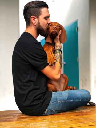 photo of man kissing his dog