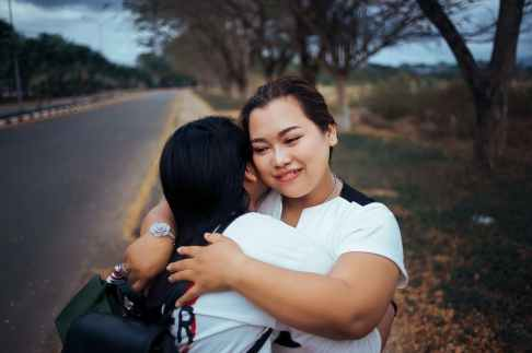 two women hugging each other standing on pathway of the road